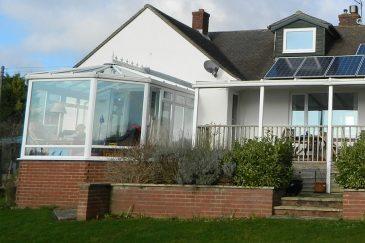 White uPVC victorian conservatory with a veranda