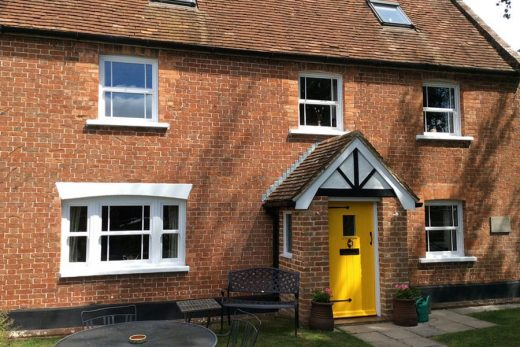 White uPVC sliding sash windows and a yellow composite door